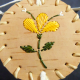 Top lid of round birch bark basket with 3 yellow pedal quill design